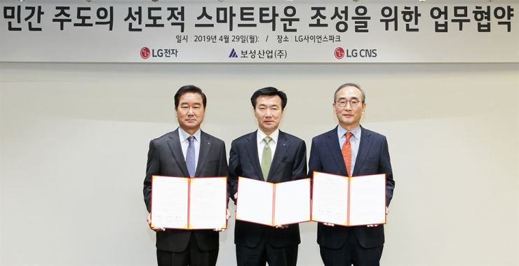 LG CNS CEO Kim Young-shub, right, poses for a photo with Choi Sang-gyu, left, head of Korea Sales Division at LG Electronics, and Kim Han-kee, vice chairman of Bosung Corporation, at LG Science Park in Magok, southwestern Seoul, Monday, after signing a business agreement to create a 'smart town' in Busan. / Courtesy of LG CNS