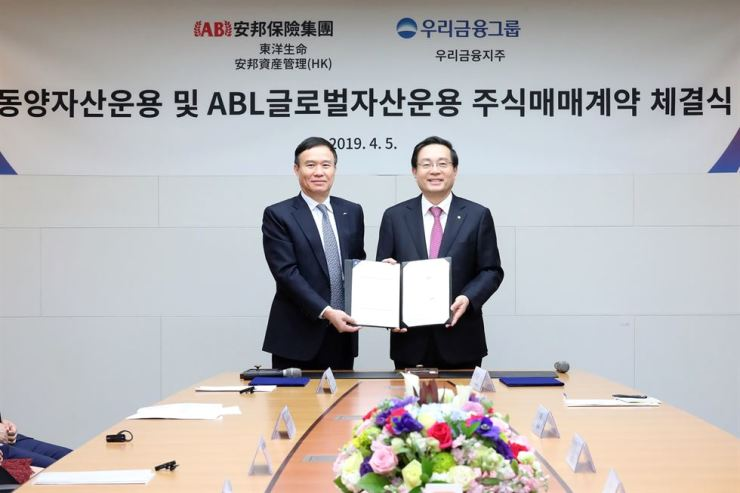 Woori Financial Group Chairman Sohn Tae-seung, right, poses with Tongyang Life Insurance CEO Luo Jianrong after agreeing to acquire ABL Global Asset Management and Tongyang Asset Management at a Woori Bank branch in central Seoul, Friday. Courtesy of Woori Financial Group