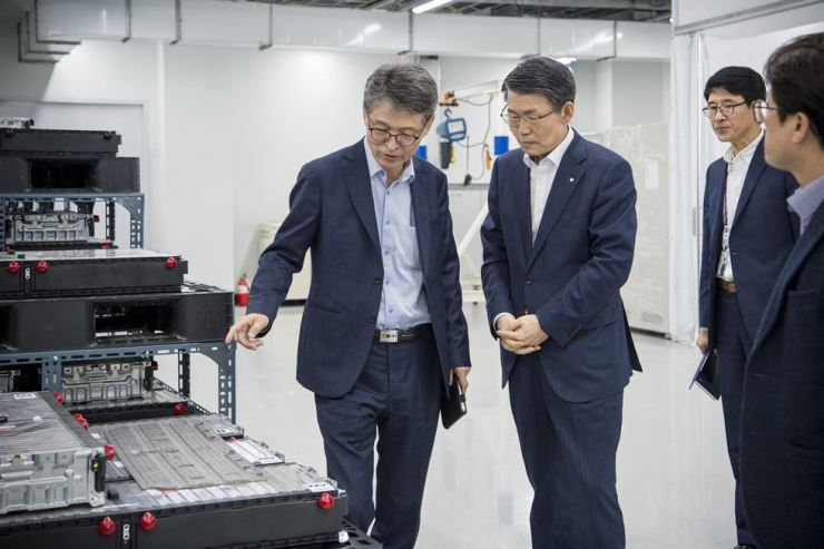 Eximbank Chairman Eun Sung-soo, right, is briefed by Powerlogics CEO Kim Won-nam about the products of the company, which produces parts for large IT firms, at the firm's production plant in Cheongju, North Chungcheong Province, Wednesday. Eximbank said Thursday it would provide a total 9.5 trillion won in funds for innovative businesses. / Courtesy of Eximbank