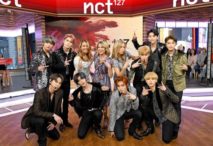 NCT 127 members pose with the hosts of 'Good Morning America' after an appearance on the ABC talk show, April 18. Korea Times file