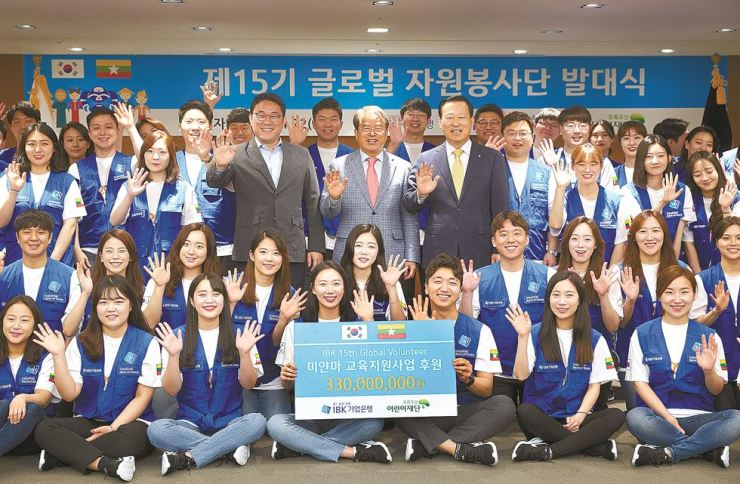 Industrial Bank of Korea (IBK) Chairman Kim Do-jin, third row fifth from left, and ChildFund Korea CEO Lee Je-hoon, third row fourth from left, pose with volunteers after an event marking the launch of IBK's 15th global volunteer team at the bank's headquarters in central Seoul, Monday. The state-run lender also donated 330 million won ($288,916) to ChildFund Korea to improve education in Yangon, Myanmar. / Courtesy of IBK