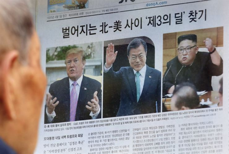 A man reads a newspaper showing photos, from left of U.S. President Donald Trump, South Korean President Moon Jae-in and North Korean leader Kim Jong-un in Seoul, South Korea, April 11. AP-Yonhap