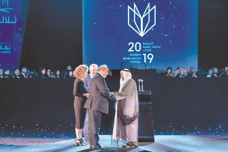 His Highness Sheikh Dr. Sultan bin Muhammad Al Qasimi, Supreme Council Member and Ruler of Sharjah, right, receives the banner for the World Book Capital from Markos Bolaris, Greek Deputy Minister of Foreign Affairs, during an inauguration ceremony of Sharjah World Book Capital 2019 at the Al Majaz Amphitheatre in Sharjah, the United Arab Emirates, Tuesday. Courtesy of Sharjah Govt Media Bureau