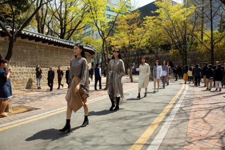 Models donning Bowlloon's spring collection walk down the street next to Deoksu Palace walls as part of Seoul 365 Fashion Show, Monday. 월요일 서울 365 패션쇼의 일환으로, 모델들이 디자이너 브랜드 '보울룬' 의 스프링 컬렉션을 입고 덕수궁 돌담길을 걷고 있다. /Courtesy of Seoul Metropolitan Government