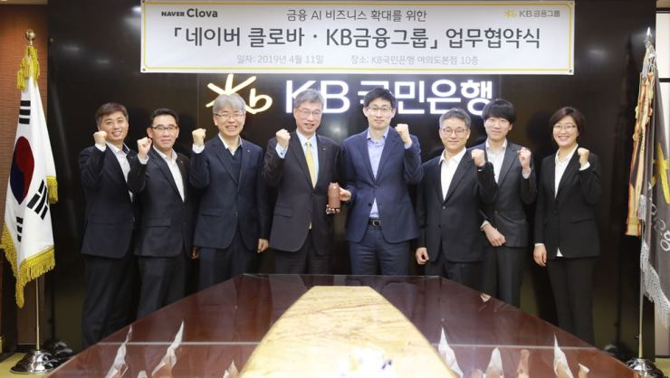KB Kookmin Bank CEO Hur Yin, fourth from left, and Naver Search & Clova CEO Shin Jung-ho, fourth from right, raise their fists with officials from the bank and the IT subsidiary of Korea's largest portal, at the bank's headquarters on Yeouido, Seoul, April 11. The two firms agreed to foster cooperation to enhance artificial intelligence-based financial services. Courtesy of KB Kookmin Bank