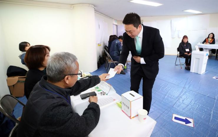 Minor opposition Bareunmirae Party Rep. Lee Jae-hwan, a candidate for Wedneday's bi-election, receives a ballot at voting staion No. 9 set up at a senior citizens' community center in an apartments village in Changwon's Seongsan-gu district in South Gyeongsang Province, Wednesday. Yonhap