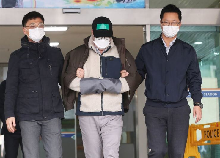 Robert Holley, a TV celebrity, is escorted out of Nambu Police Station in Suwon, Wednesday, for the court's decision about his continued detention for allegedly using methamphetamine. He was released but a probe into his drug use allegation will continue. Yonhap