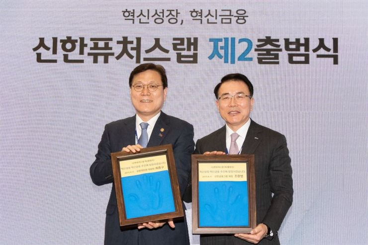 Financial Services Commission Chairman Choi Jong-ku, left, and Shinhan Financial Group Chairman Cho Yong-byoung pose with framed copies of their handprints at the opening of Shinhan's expanded startup center in Jung-gu, Seoul, Thursday. Courtesy of Financial Services Commission
