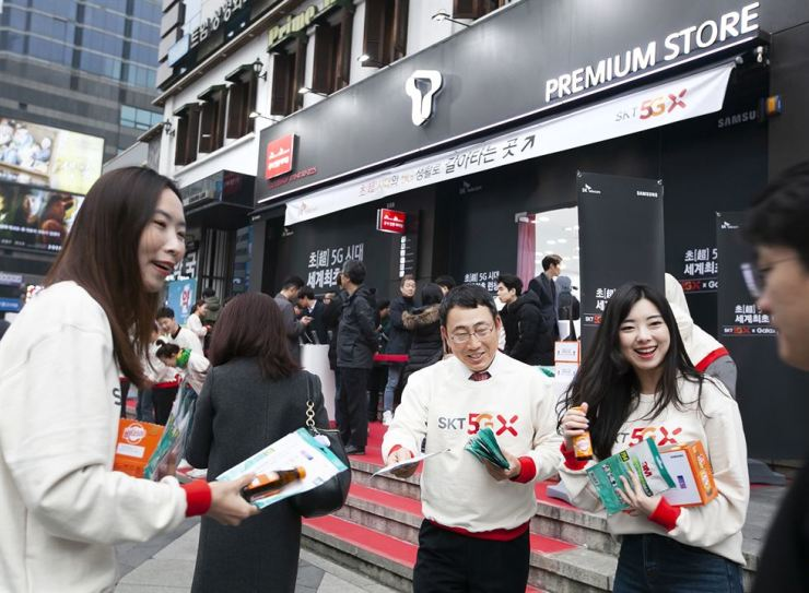 Yoo Young-sang, second from right, head of SK Telecom's MNO business, and models distribute pamphlets to promote the firm's 5G services, in front of one of its stores in Gangnam, Friday. / Courtesy of SK Telecom