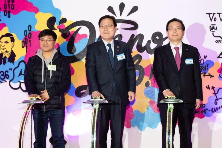 Financial Services Commission Chairman Choi Jong-ku, center, and Woori Financial Group Chairman Sohn Tae-seung, right, push a button with an entrepreneur to open Woori Bank's expanded center for fintech startups in Yeouido, Seoul, Wednesday. Sohn said Woori will invest 130 billion won in innovative companies. Courtesy of Financial Services Commission