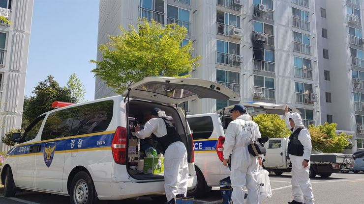 Forensic science officers prepare to inspect the scene of an arson and knife attack by a reportedly schizophrenic man at an apartment building in Jinju, South Gyeongsang Province, Wednesday. /Yonhap