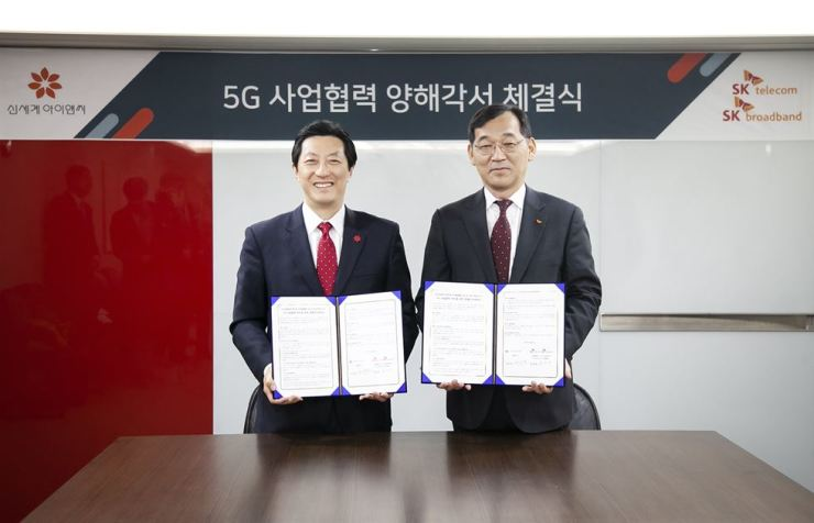Yoon Won-young, right, in charge of media business at SK Telecom, and Shinsegae I&C CEO Kim Jang-wook pose for a photo after signing an MOU to develop 5G-based shopping services at Shinsegae I&C's headquarters in Seoul, Tuesday. / Courtesy of SK Telecom