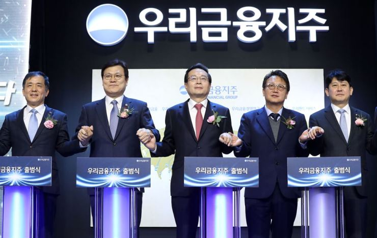 Woori Financial Group Chairman Sohn Tae-seung, center, and Financial Services Commission Chairman Choi Jong-ku, second from left, with other dignitaries at a ceremony marking the launch of the group's holding firm at Woori Bank's headquarters in Seoul on Jan 14. / Korea Times file