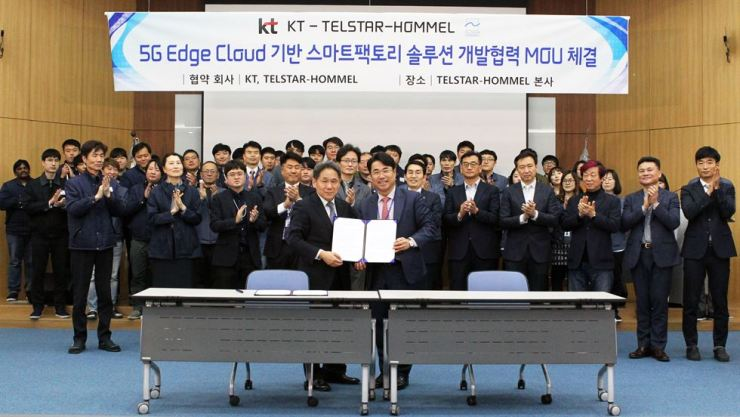 Lee Jae-pil, left in front row, head of marketing division at KT, poses with Im Byung-hoon, CEO of Telstar-Hommel, at the latter's headquarters in Pyeongtaek, Gyeonggi Province, Friday, after signing a memorandum of understanding to co-develop smart factory platforms using the former's 5G network technology. / Courtesy of KT