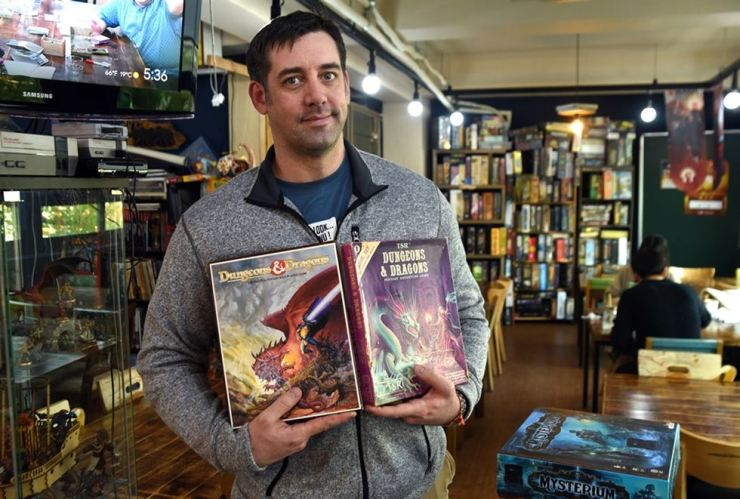 Joey Croner, owner of Dice Latte and co-organizer of GoblinLatte Con, holds his English and Korean copies of the Dungeons & Dragons playbooks. / Korea Times photo by Jon Dunbar