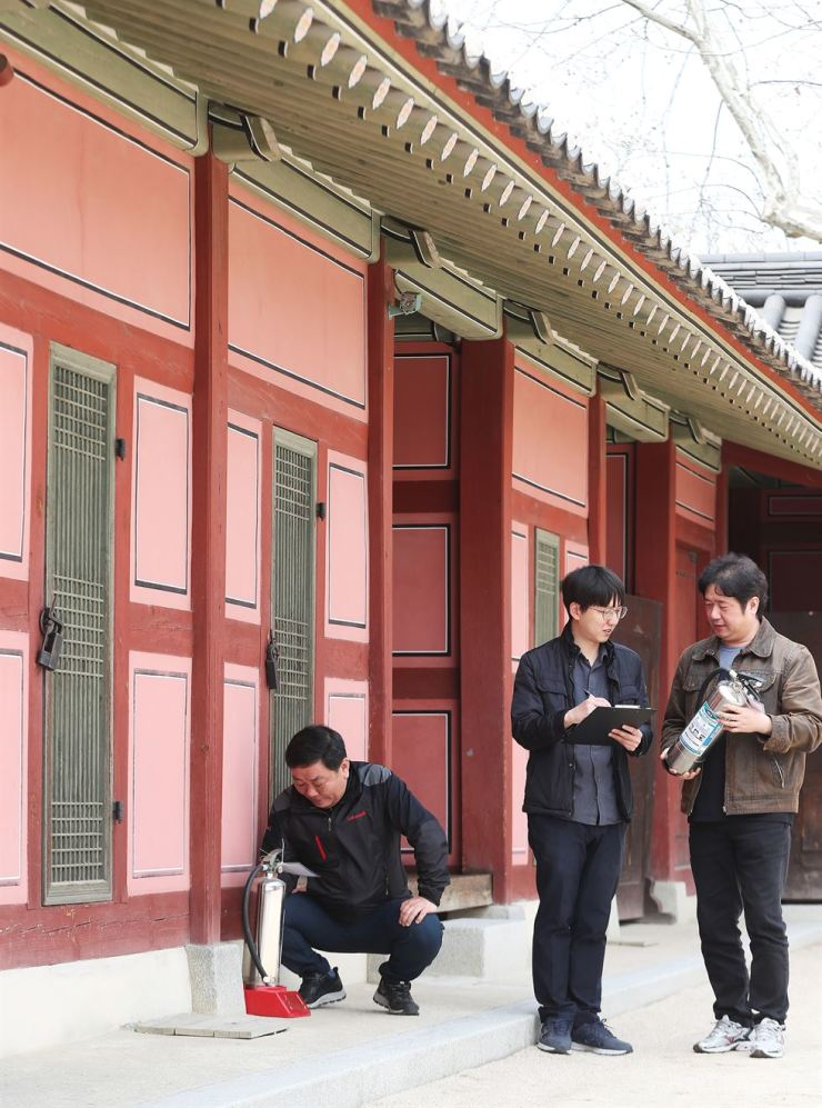 Officials of Suwon City check fire extinguishers at Hwaseong Haenggung in Suwon, Gyeonggi Province, Friday. The checkup on the cultural heritage comes after France's historic Notre Dame Cathedral suffered extensive damage in a massive fire. /Yonhap