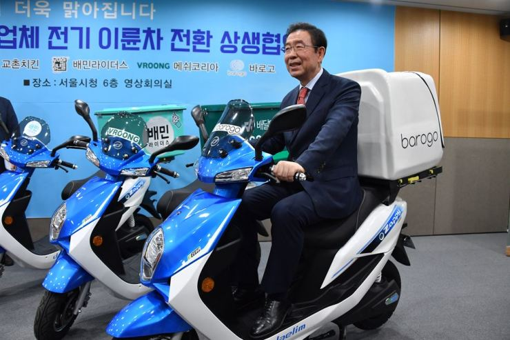 Seoul Mayor Park Won-soon s8its on an eco-friendly electric scooter at Seoul City Hall, Wednesday, after signing a memorandum of understanding with six food franchises and delivery service providers to replace gas-powered scooters with electric ones to reduce fine dust. Yonhap