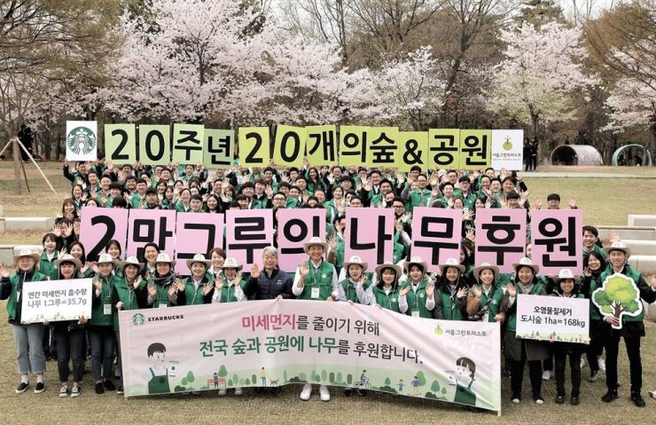Starbucks Coffee Korea employees and workers from its business partners take part in a tree-planting campaign at Seoul Forest in Seoul, Tuesday. Marking its 20th anniversary, the company raised 200 million won to donate 20,000 trees to 20 forests nationwide, including Olympic Park and Noeul Park. Courtesy of Starbucks Coffee Korea