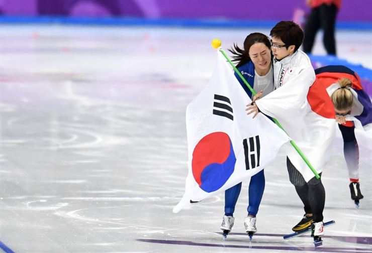 Lee Sang-hwa of Korea, left, and Nao Kodaira of Japan celebrate together after finishing the women's 500 meters at the PyeongChang Olympics on Feb. 18, 2018. Korea Times file