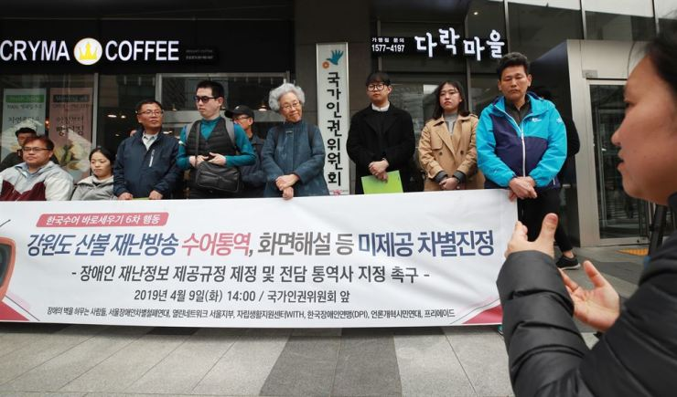 Activists rally in front of the National Human Rights Commission building, downtown Seoul, Tuesday, to condemn the lack of sign language interpretation in recent Gangwon Province fire reports by news broadcasters. Yonhap