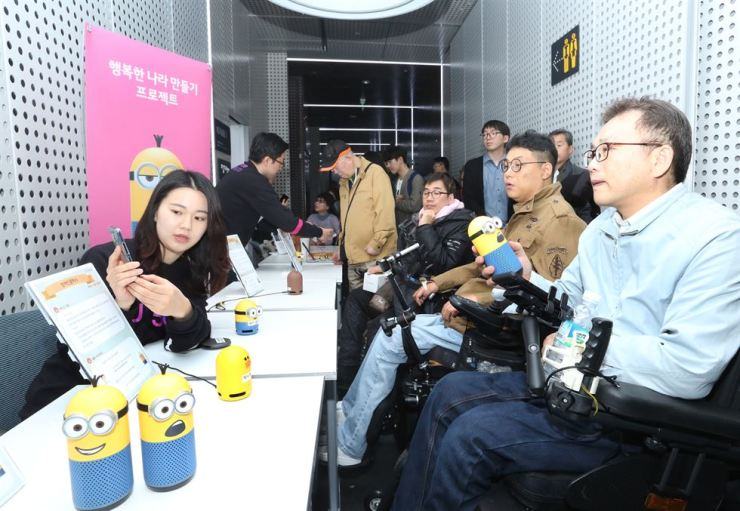 Physically challenged persons try out call taxi services for the disabled and other services designed exclusively for them through AI speakers donated by LG Uplus and Naver during a media event in Seoul, Wednesday. / Courtesy of LG Uplus