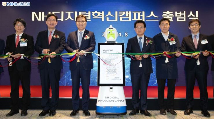 Financial Services Commission Choi Jong-ku, third from left, cuts a ribbon with NongHyup Financial Group Chairman Kim Gwang-soo, third from right, NongHyup Bank CEO Lee Dae-hoon, second from left, and other officials open NongHyup's innovation center in Yangjae-dong, Seoul, Monday. Courtesy of NongHyup Financial Group