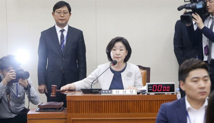 Rep. Sim Sang-jeung, head of the special parliamentary panel on political reform, knocks the gavel at the National Assembly in Seoul, Tuesday, after parties agreed to fast-track an electoral reform bill. Yonhap