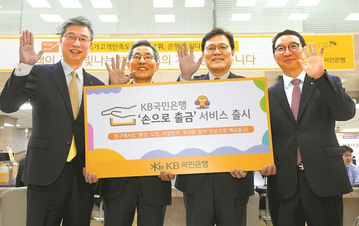 Financial Services Commission Chairman Choi Jong-ku, second from right, poses with KB Financial Group Chairman Yoon Jong-kyoo, second from left, and KB Kookmin Bank CEO Hur Yin, left, at KB Kookmin Bank's head office on Yeouido in Seoul, Friday. On the day, KB Kookmin Bank introduced the vein-based banking authentication system that identifies individuals through the unique pattern of veins in their fingers. / Courtesy of KB Kookmin Bank