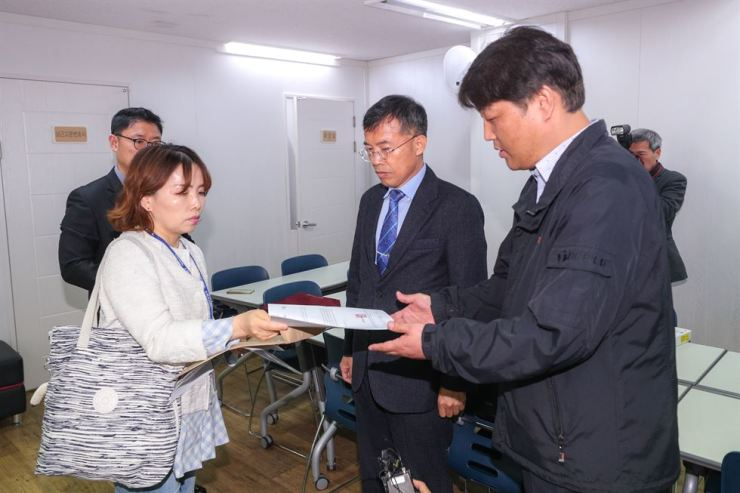 Lee Jeong-suk, left, an official of the Seoul Metropolitan Office of Education, hands over a notification letter revoking the license for the Korea Kindergarten Association to the association's Secretary General Kim Cheol, at the group's office in Yongsan-gu, Seoul, Monday. / Yonhap.