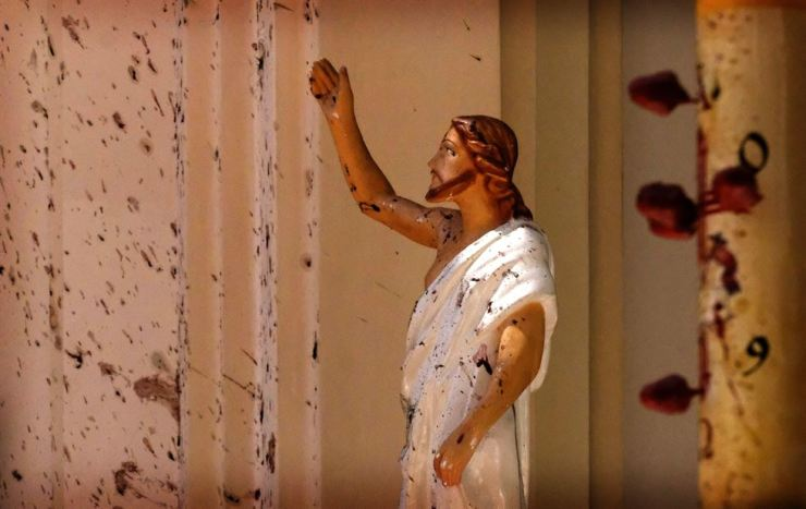 Blood stains the wall and a Jesus Christ statue at St. Sebastian's Church, after terrorist attacks in Negombo, north of Colombo, Sri Lanka, April 21. AP