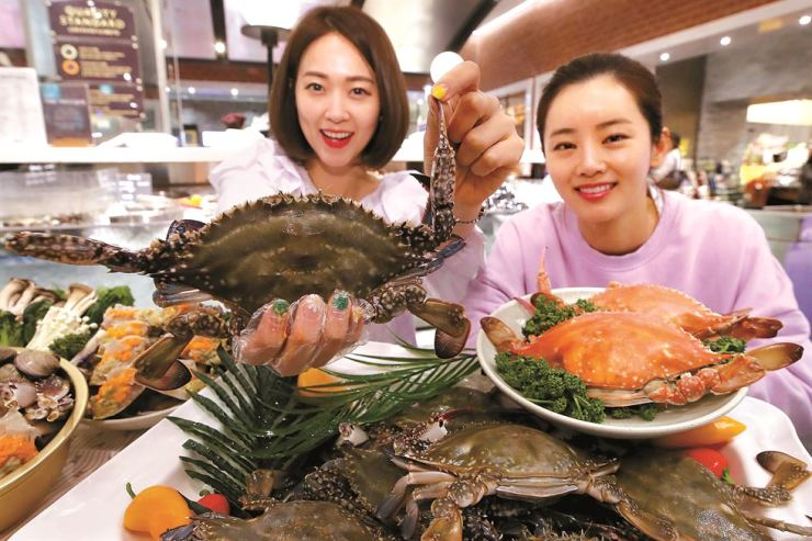 Models display crabs at the main Shinsegae Department Store location in central Seoul, Monday. Shinsegae Department Store has teamed up with local fisheries and markets to offer large crabs at 6,980 won ($6) per 100 grams in its main location, as well as its Gangnam, Yeongdeungpo and Gyeonggi branches. Yonhap