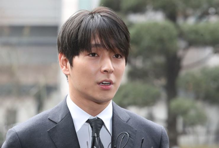 K-pop band FT Island member Choi Jong-hoon answers reporters' questions while presenting himself at Seoul Metropolitan Police Agency to be questioned over his alleged sharing in mobile chatrooms of spycam videos of him having sex with various women, March 16. / Yonhap