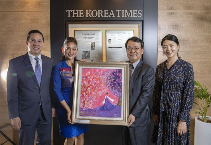 From left, Raul S. Hernandez, Philippine Ambassador to Korea, his wife Ana Algabre Hernandez and Lee Byeong-eon, President of The Korea Times, pose after Ana Algabre Hernandez donates her painting 'The Color of Joy' to The Korea Times. Korea Times photo t