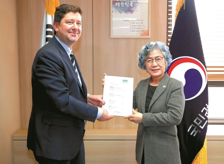 Anti-Corruption and Civil Rights Commission Chairwoman Pak Un-jong, right, and an official from Transparency International hold an agreement signed to foster cooperation between the organizations ahead of the 2020 International Anti-Corruption Conference in Seoul after signing it at the commission's headquarters in Seoul, Friday. Courtesy of the Anti-Corruption and Civil Rights Commission