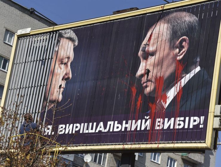 A communal worker disassembles a billboard of acting President and Presidential candidate Petro Poroshenko, left, pictured face to face with Russian President Vladimir Putin in the western Ukrainian city of Lviv, April 15, 2019. The run-off vote of the Presidential elections will take place in Ukraine on 21 April 2019. EPA-Yonhap