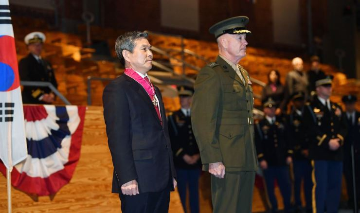 Defense Minister Jeong Kyeong-doo stands to attention after receiving the Legion of Merit, a top U.S. government decoration given to foreign military personnel, from his former counterpart, U.S. Joint Chiefs of Staff Chairman Gen. Joseph Dunford, at the Joint Base Myer-Henderson Hall, Virginia, Tuesday. / Courtesy of Ministry of National Defense