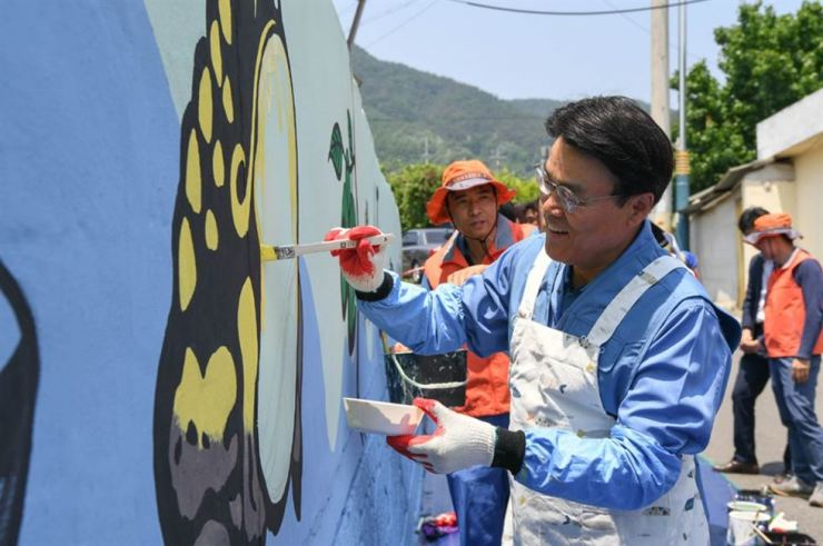 POSCO Chairman Choi Jeong-woo paints a mural in a small village near POSCO's steel mill in Gwangyang, South Jeolla Province, May 24. Courtesy of POSCO