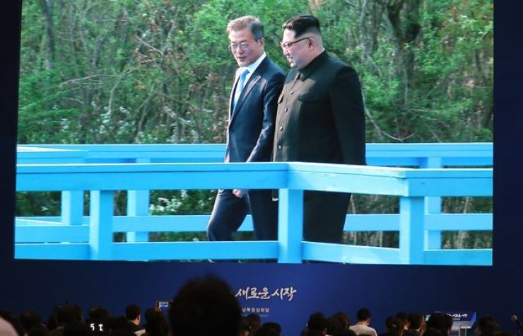 President Moon Jae-in and North Korean leader Kim Jong-un walk on a boardwalk bridge in the truce village of Panmunjeom during their April summit. Korea Times