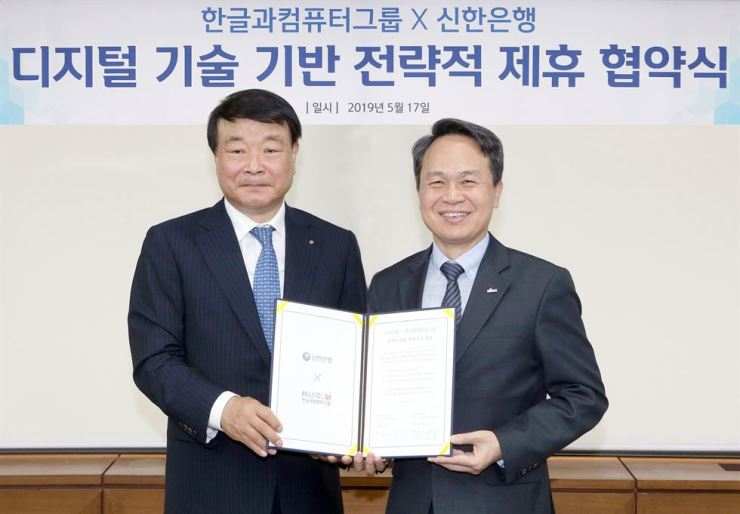 Shinhan Bank CEO Jin Ok-dong, right, and Hancom CEO Kim Sang-chul pose after agreeing on strategic digital ties at Shinhan Bank's office in Seoul, Friday. Courtesy of Shinhan Bank.