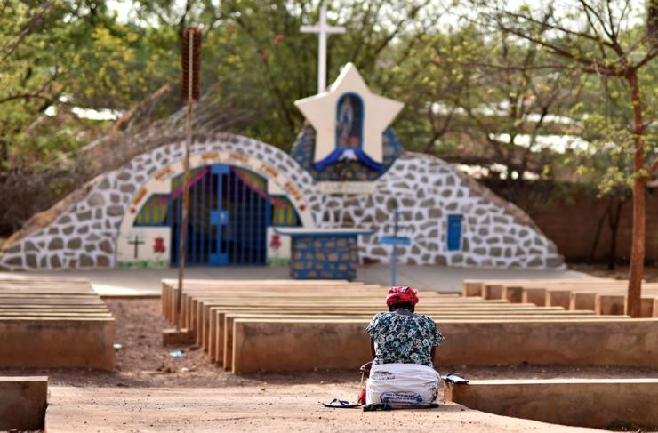 A woman prays near a statue of Virgin Mary outside the cathedral of Our Lady of Kaya in the city of Kaya, Burkina Faso, May 16. Reuters