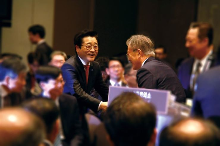 Starkey Korea CEO Richard Shim, left, shakes hands with President Moon Jae-in during the Korea Chamber of Commerce & Industry conference at the lobby group's head office in Seoul in this May 10, 2017 file photo. / Courtesy of Starkey Korea