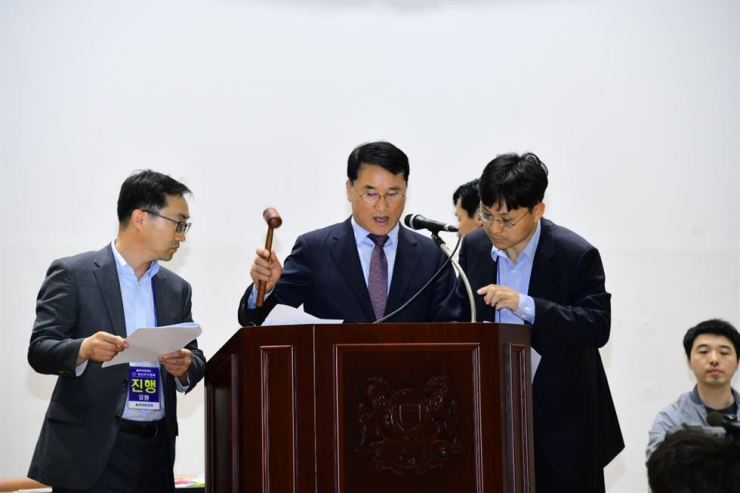 Hyundai Heavy Industries CEO and President Han Young-seok, center, announces shareholders' approval of the company's split-up proposal in their meeting held in a gymnasium at the University of Ulsan, Friday. Courtesy of Hyundai Heavy Industries