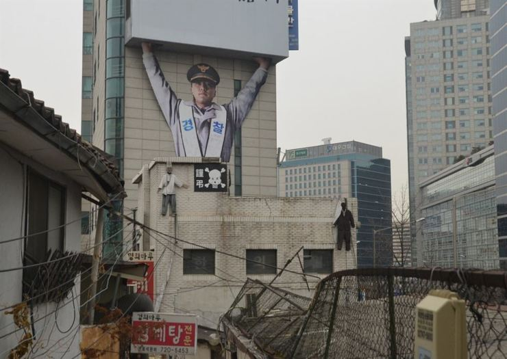 Two human figures representing evicted business owners hang from a building slated for remodeling, beneath a giant figure of a police officer, in Saemunan Village, on Jan. 29, 2016. The area was renovated into Donuimun Museum Village which opened in April 2018. / Korea Times photo by Jon Dunbar