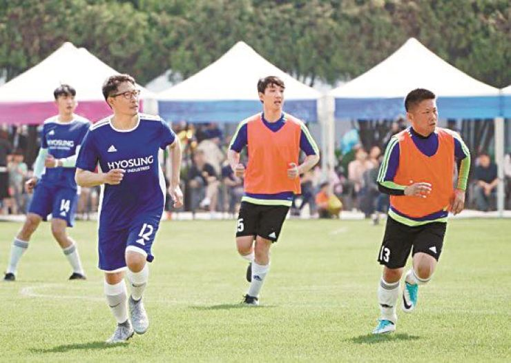 Hyosung Group Chairman Cho Hyun-joon, second from left, plays for Hyosung Heavy Industries team during a football match against Hyosung TNC at Anyang Plant in Gyeonggi Province, Saturday. About 3,400 employees and their family members joined the company's outdoor sports activities. Courtesy of Hyosung