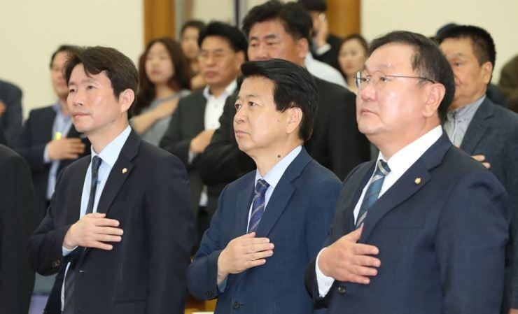 Candidates in the floor leader race of the ruling Democratic Party of Korea (DPK) pledge allegiance to the flag in a seminar at the National Assembly, Tuesday. From left are, Reps. Lee In-young, Noh Woong-rae and Kim Tae-nyeon. The new floor leader of the DPK is tasked with resolving the recent dissonance with the main opposition Liberty Korea Party created by the differences over fast-tracking reform bills and winning in the 2020 elections and supporting the third year of Moon Jae-in administration in a long term. / Yonhap