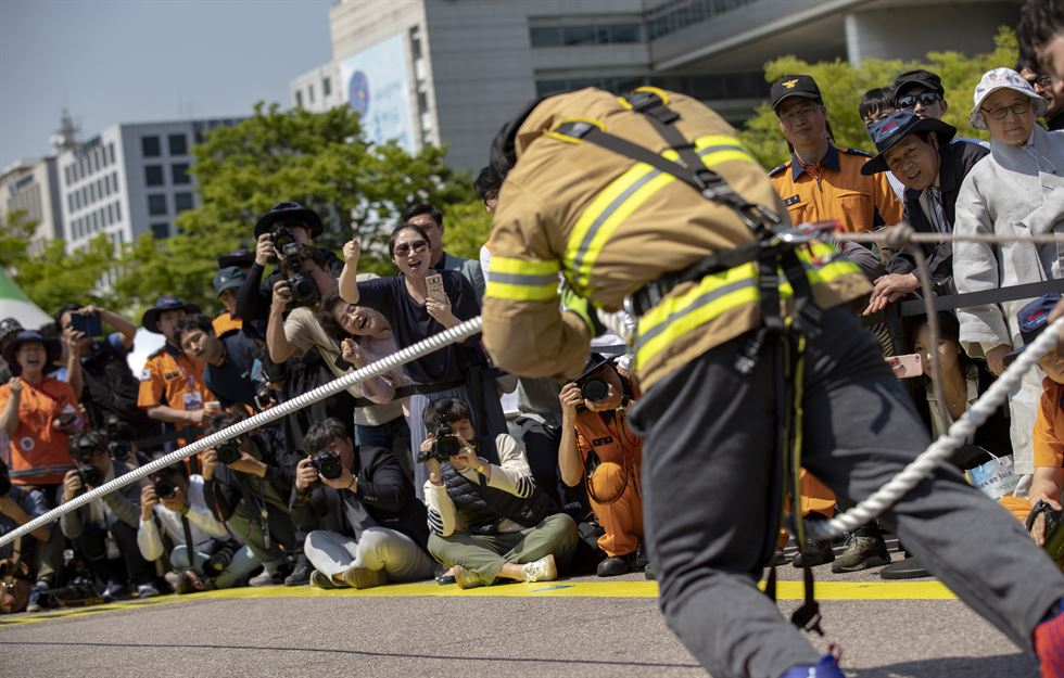 A firefighter pulls a rope tied to an 11-ton fire engine in the second 'Strong Men' festival at a public park in Yeouido, Seoul, Thursday. Korea Times photo by Shim Hyun-chul