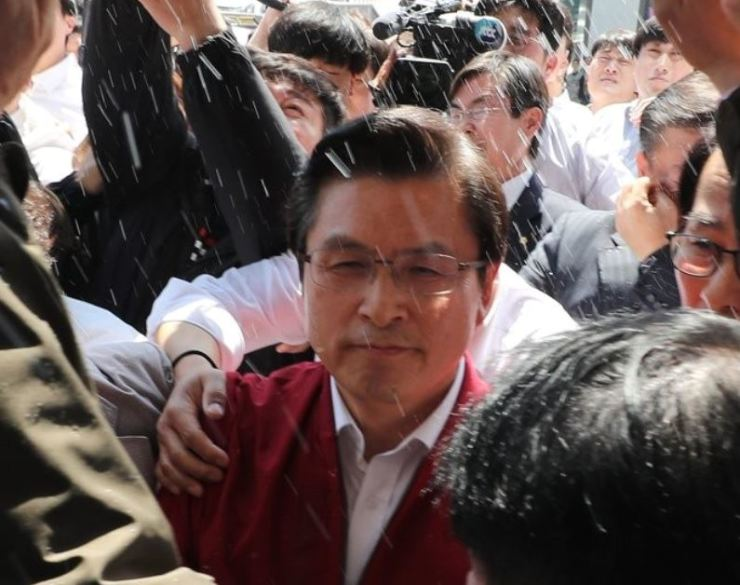 Hwang Kyo-ahn, chairman of the main opposition Liberty Korea Party, is doused with water on his way to Songjeong railway station while facing fierce opposition from the public in Gwangju, Friday. Yonhap