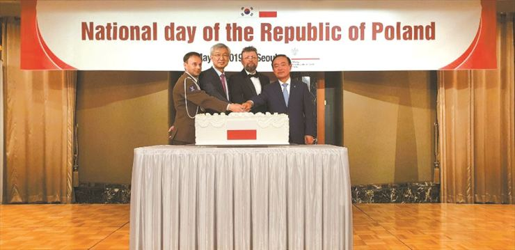 Polish Ambassador to Korea Piotr Ostaszewski, third from left, Polish Defense Attache Colonel Swiatek, left, First Vice Foreign Minister Lee Tae-ho, second from left, and ruling Democratic Party of Korea lawmaker and president of Korean-Poland Parliamentarians Friendship Association Chang Byoung-wan join a cake-cutting ceremony during a reception to celebrate the anniversary of the May 3 Polish Constitution of 1791 at Lotte Hotel in downtown Seoul, May 8. / Korea Times photo by Yi Whan-woo