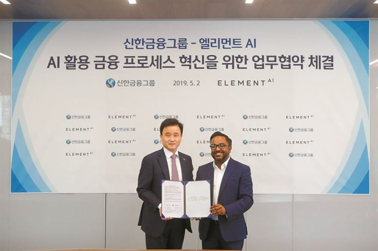 Shinhan Financial Deputy President Park Woo-hyuk, left, and Karthik Ramakrishnan, head of the advisory board at the Canada-based software developer Element AI, pose after signing an agreement to cooperate on developing artificial intelligence software at the Shinhan Future Lab in Seoul, Thursday. Shinhan joined forces with Element AI as part of the group's digital transformation. Courtesy of Shinhan Financial Group