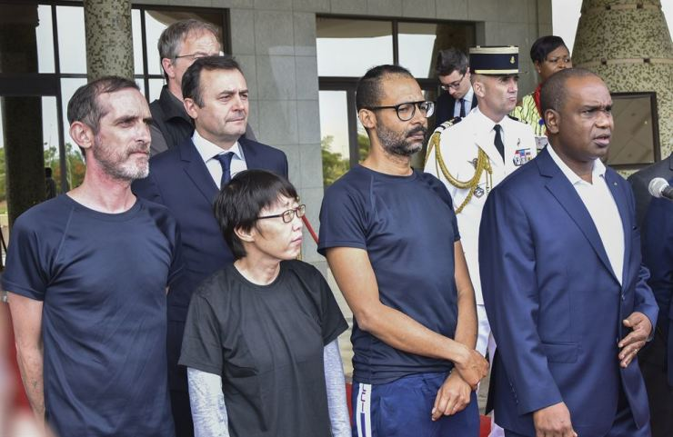 Patrick Picque from France (L) and Laurent Lassimouillas from France (3-L) and an unidentified South Korean hostage (C) stand with Burkina Faso's Foreign Minister Alpha Barry (R) at the Presidential Palace in Ouagadougou, Burkina Faso 11 May 2019. According to the the French presidency the French army has released four hostages during an intervention in northern Burkina Faso. Two are French, one American and one South Korean citizen. Two French soldiers are reported to have been killed in the operation to free the hostages. The two French citizens were kidnapped 01 May 2018 in Benin. EPA